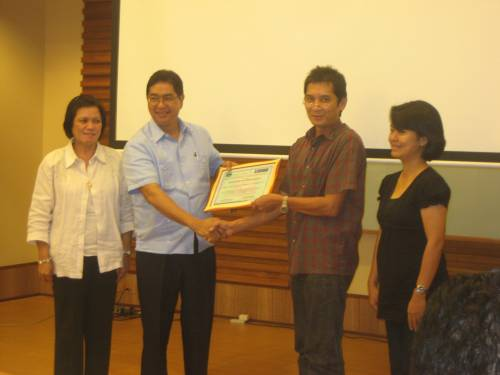 Engr. Recabo, Jr. and Ms. Hernandez present the Certificate of Recognition to General Manager Manda